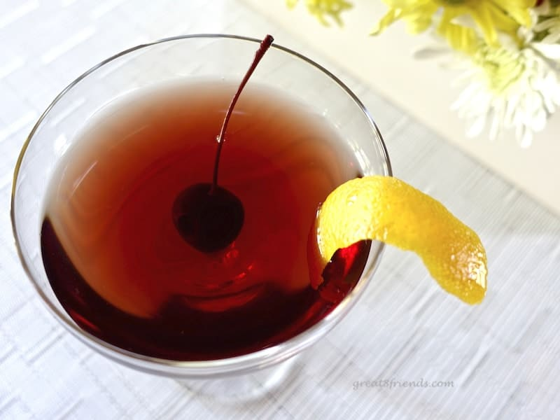 An overhead shot of the Cherry Manhattan Cocktail with a cherry and orange zest garnish.