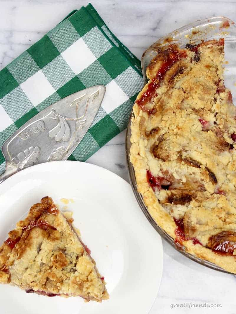 A cut piece of French Apple Cranberry Pie with a buttery crumb topping.