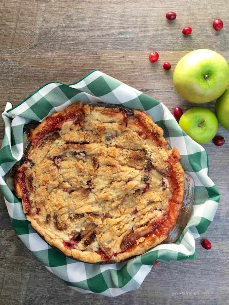Overhead view of a pie made with apples, cranberries and a buttery crumb topping.