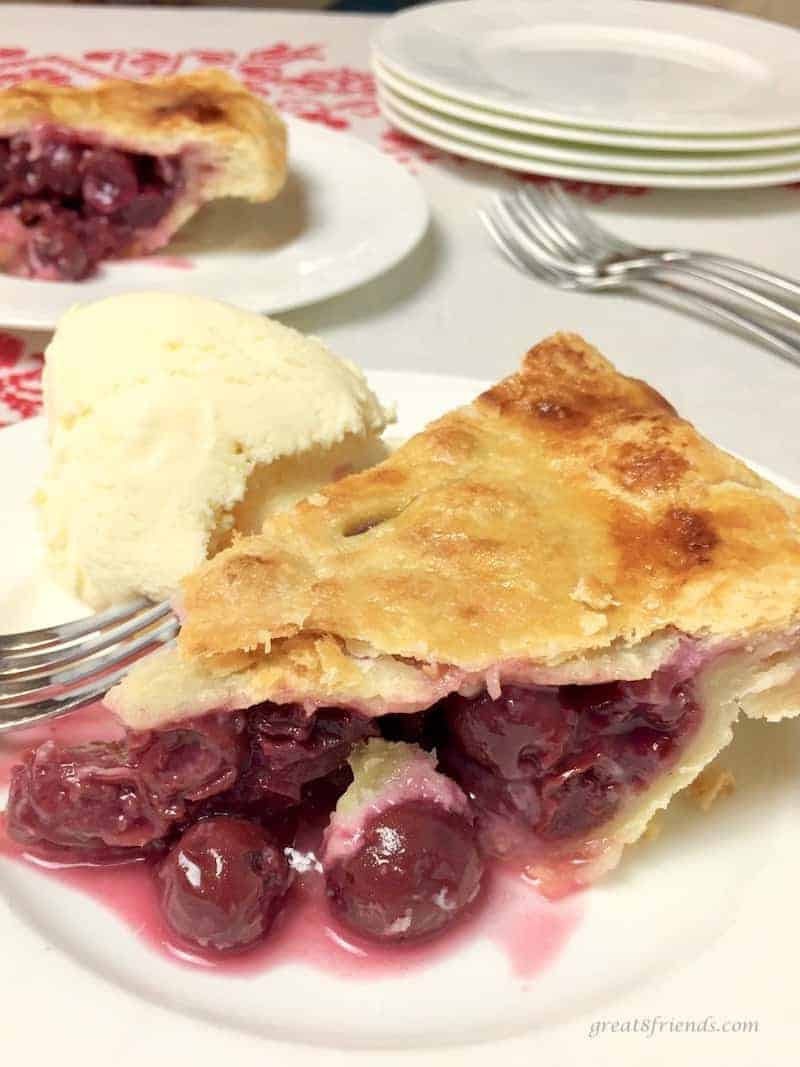 Slice of All-American Cherry Pie with a scoop of ice cream.