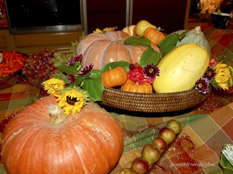 A centerpiece of pumpkins, gourds and flowers.