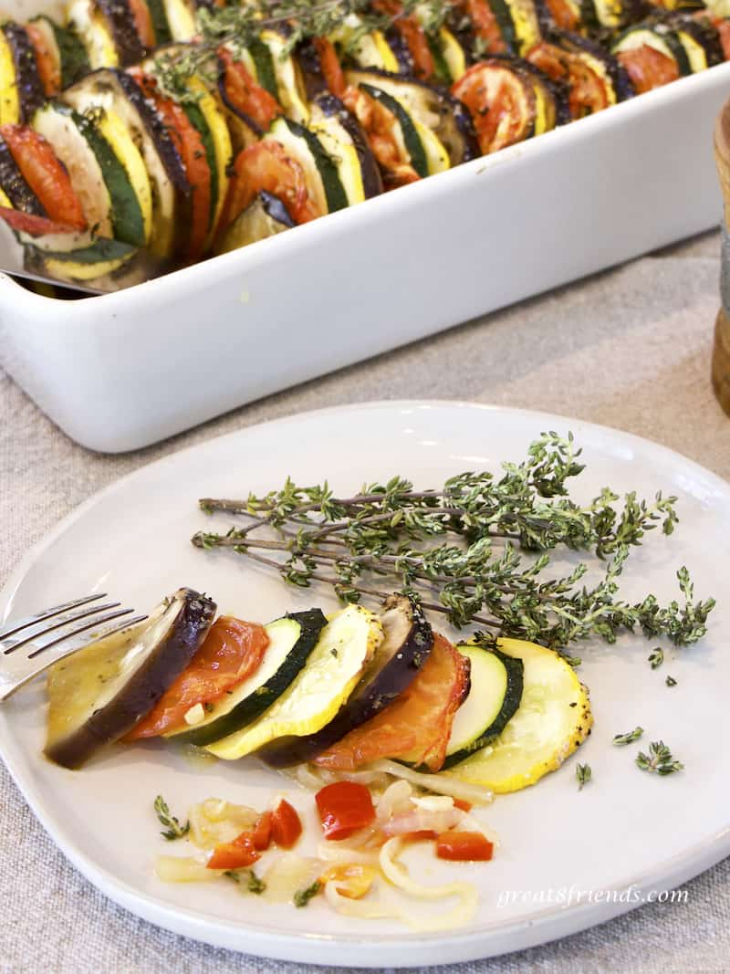 A serving of Provençal Vegetable Tian on white plate garnished with thyme