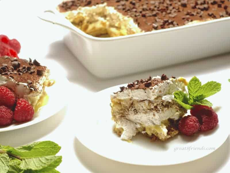 a serving of Tiramisu with the whole dish in the background