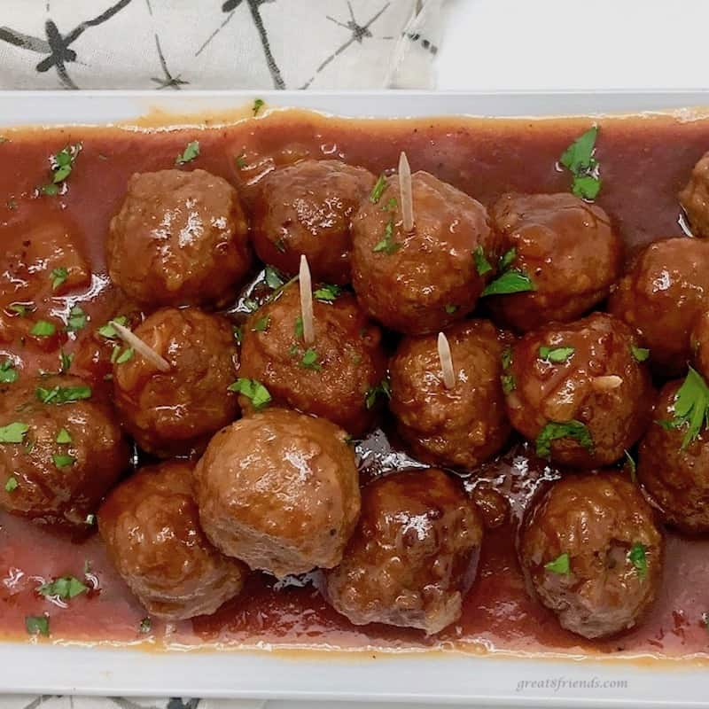 Up close photo of Hawaiian Meatballs on a platter with sauce and toothpicks for eating.