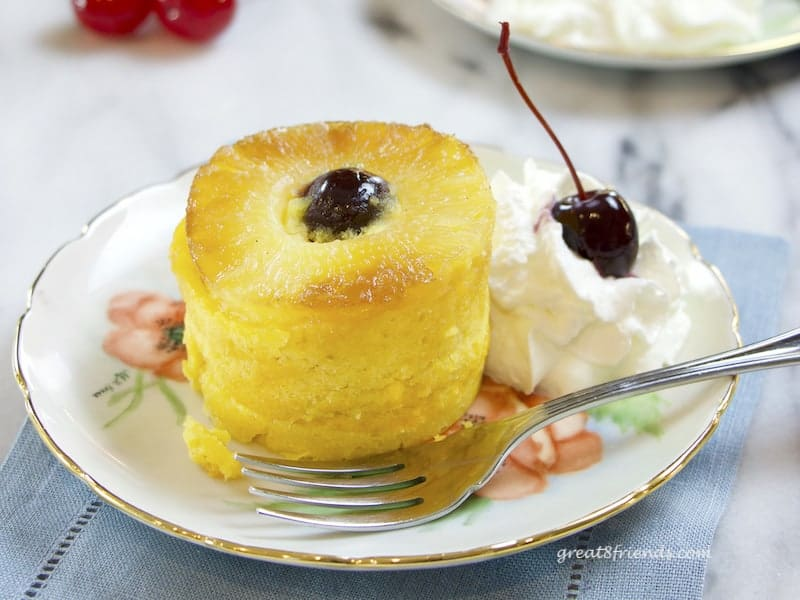 Individual serving of Pineapple Upside Down Cake with whipped cream and a cherry on the side.