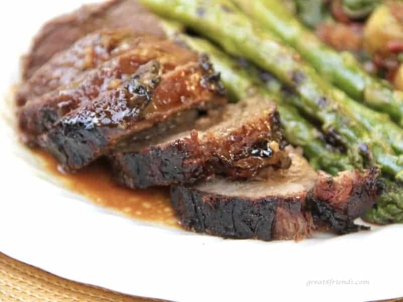 Grilled and sliced leg of lamb served with a marinade sauce and grilled asparagus.
