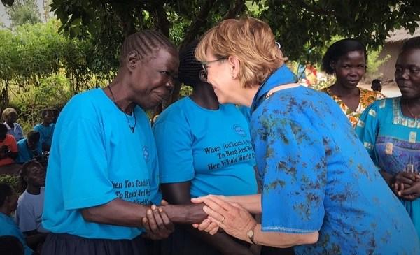Karon shaking hands with a Ugandan woman.