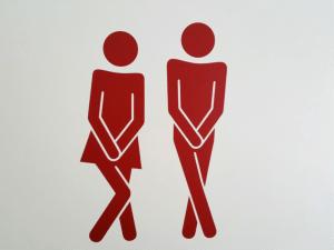 twee rode figuurtjes die ongemakkelijk hun hand voor hun kruis houden