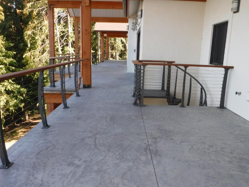 Decorative concrete dresses the upper deck. Custom cable rails surround.