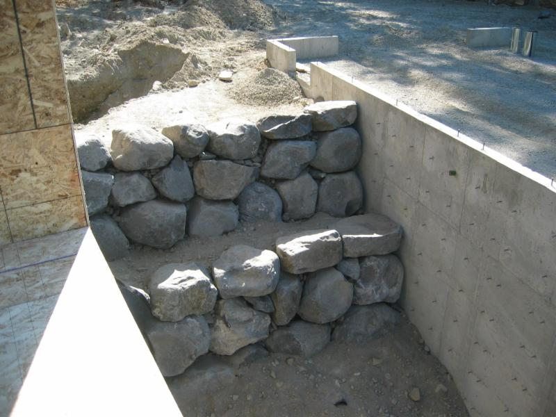 Boulder retaining walls create the walkway between house and garage.