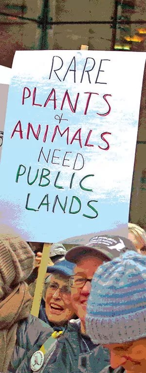 """A woman holding up a sign """"Rare plants and animals need public lands"""""""