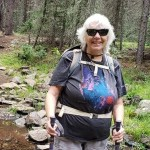 A woman with sunglasses on hiking in a forest
