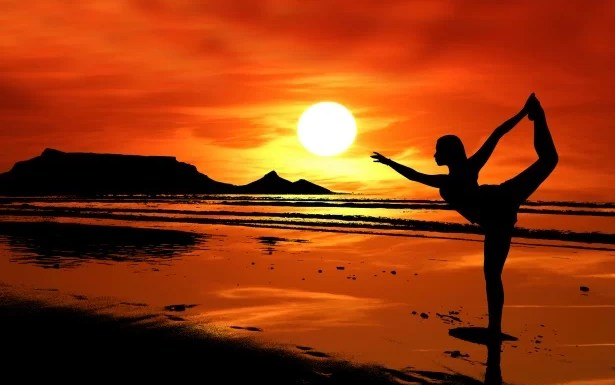Woman on Beach Practising Yoga at Sunset