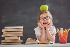 child at school with apple on her head