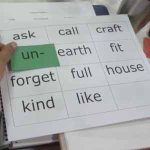 "Hand moving the prefix ""un"" over grid of words"