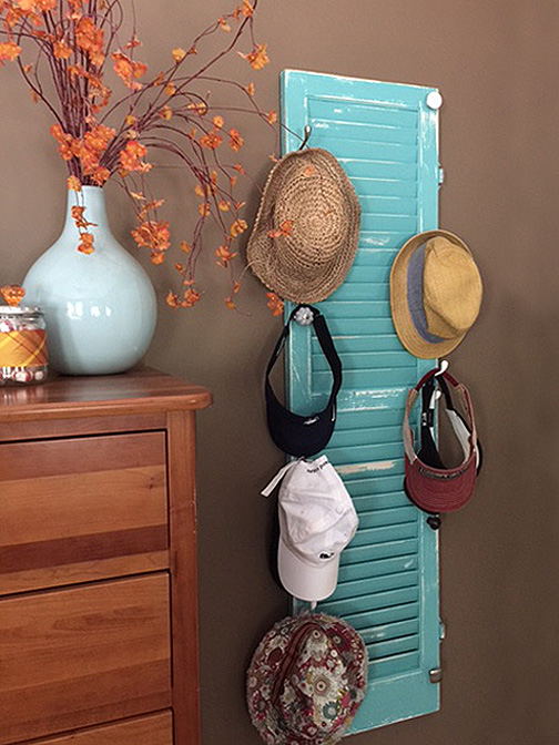 DIY hat hook from an old shutter with a variety of hooks and knobs is just what you need for an inexpensive storage solution and a way to organize all your hats. Benjamin Moore Gulf Stream paint was the perfect color for this piece.