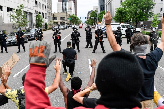 A man kneels before police in the middle of a street as others standing behind the man hold up their hands.