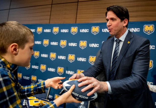 GREELEY, CO - July 24: Ed McCaffrey autographs a Denver Broncos football for young fan Paul Hulac, 11, left, during a press conference introducing former Denver Broncos player Ed McCaffrey as the new University of Northern Colorado Bears head football coach in the Campus Commons on the UNC campus in Greeley Friday, Dec. 13, 2019. McCaffrey spoke about his transition during the Big Sky media days this week. (Alex McIntyre/Staff photographer)
