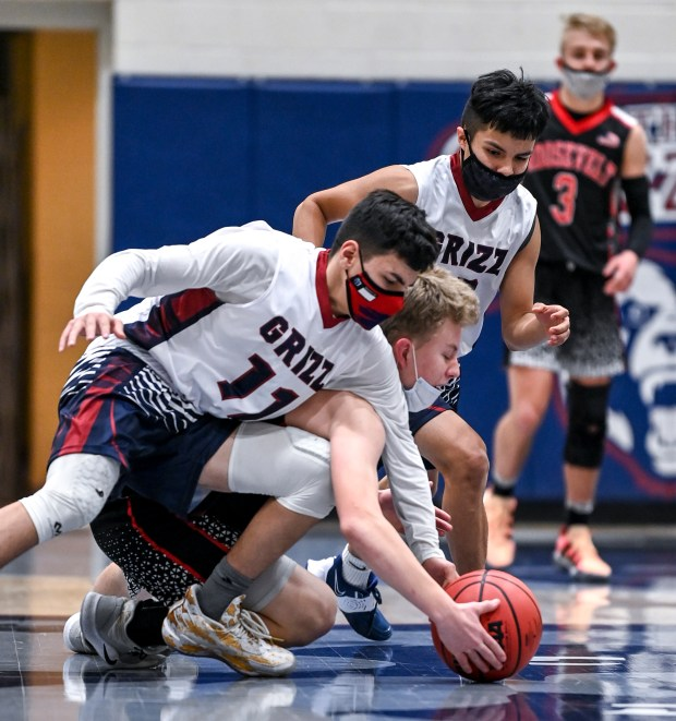 GREELEY, CO - FEBRUARY 09:Northridge's Moses Escobar (11) and Northridge's Victor Gonzales (10) fight Roosevelt's Austin Kendall (24) for possession on the floor during the Northridge Grizzlies boys basketball game against the Roosevelt Roughriders at Northridge High School in Greeley Feb. 9, 2021. The Roughriders took down the Grizzlies 58-44.(Alex McIntyre/Staff Photographer)