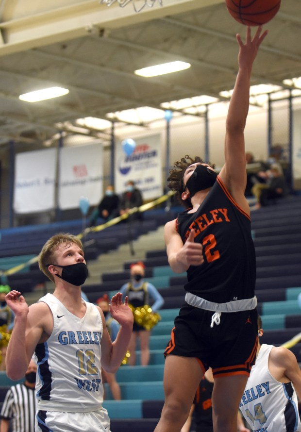 GREELEY, CO - FEBRUARY 15:Greeley Central's Isaiah Flores makes a layup as he passes Greeley West's Colton Gillingham during the Greeley Central Wildcats boys basketball game against the Greeley West Spartans at Greeley West High School in Greeley Monday, Feb. 15, 2021. (For the Tribune/ Joshua Polson)