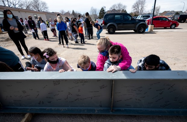GREELEY, CO - MARCH 25:Miss Tasha, in pink, helps student Jace Stevenson sign the beam alongside other students during the topping ceremony for the bond-funded expansion of S. Christa McAuliffe STEM Academy in Greeley March 25, 2021. In the ceremony, the final main structural beam, weighing more than half a ton, was hoisted into position atop the structure and fastened. Students, teachers and administrators signed their names on the beam before it was lifted into place. (Alex McIntyre/Staff Photographer)