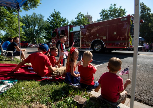 GREELEY, CO - JULY 03:A group of siblings and cousins watch and wave as the Greeley Fire Department passes by during the Independence Day Parade in Greeley July 3, 2021. A mother of a few of the kids, Nikki Shaw, said that the family has been coming to the parade for at least 15 years as a staple of their Fourth of July celebrations. The parade, held on July 3 this year because the 4th fell on a Sunday, draws thousands to watch each year. (Alex McIntyre/Staff Photographer)