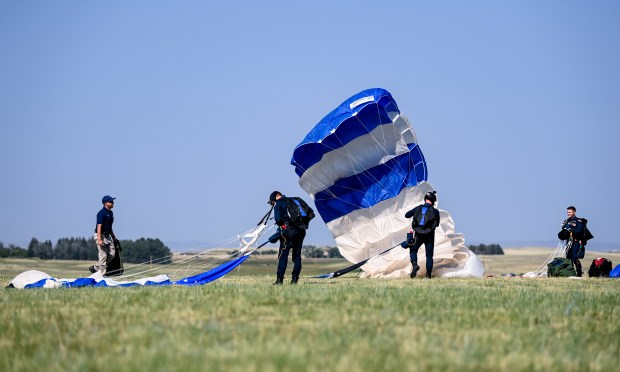 CHEYENNE, WY - JULY 28:Cadets from the U.S. Air Force Academy pack up their parachutes after parachuting out of a UV-18 Twin Otter during the 2021 annual Wings Over Warren air show at Francis E. Warren Air Force Base in Cheyenne, Wyo. July 28, 2021. The air show featured parachute jumps by U.S. Air Force Academy cadets, flyovers by a variety of aircraft and a demonstration by the U.S. Air Force Thunderbirds. (Alex McIntyre/Staff Photographer)