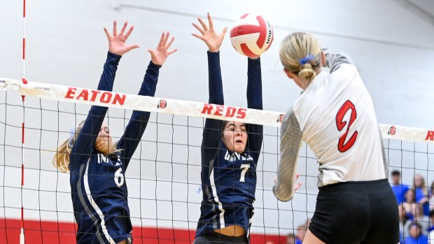 EATON, CO - SEPTEMBER 28:Eaton's Rylee Martin (2) attacks as University's Paige Heck (6) and University's Aesha Alrashed (7) leap to defend during the Eaton Reds volleyball match against the University Bulldogs at Eaton High School in Eaton Sept. 28, 2021. (Alex McIntyre/Staff Photographer)