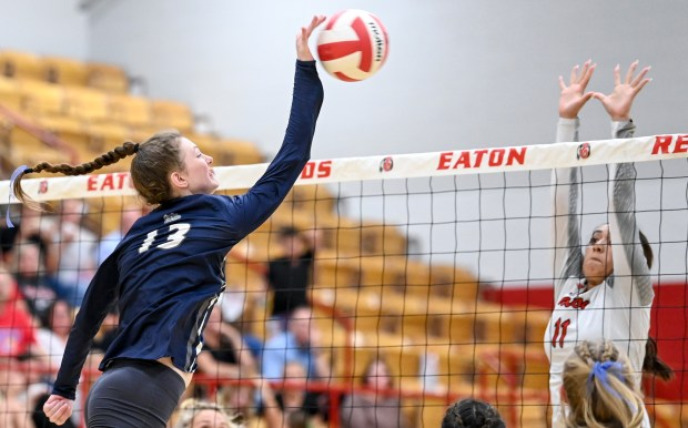 EATON, CO - SEPTEMBER 28:University's Katie Bauer (13) attacks as Eaton's Madison Chavez (11) leaps to defend during the Eaton Reds volleyball match against the University Bulldogs at Eaton High School in Eaton Sept. 28, 2021. (Alex McIntyre/Staff Photographer)
