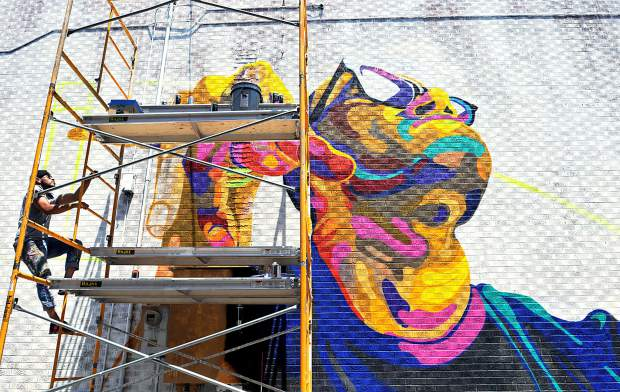 In this 2014 Tribune file photo, Armando Silva climbs the scaffolding next to a mural in an alley between 8th Street and 9th Street, in downtown Greeley. Silva was commissioned by Greeley's Downtown Development Authority and Greeley's Art Commission to create the massive mural for the alley.