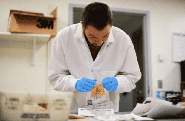 David Storey is processing the samples for COVID-19 test at Colorado Department of Public Health and Environment Laboratory Services Division in Denver, Colorado on Saturday. March 14, 2020. (Hyoung Chang/The Denver Post)
