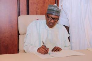 PRESIDENTBUHARI SIGNS HIS LETTER TO NATIONAL ASSEMBLY. President Buhari signs letter notifying the National Assembly of his resumption of duties flanked by the Chief of Staff at the State House Abuja on Aug 21, 2017. PHOTO; SUNDAY AGHAEZE/STATE HOUSE
