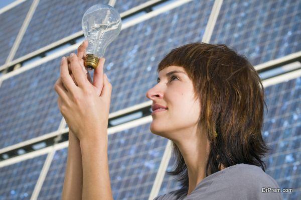 seitliche Kopf-und-Schultern-Aufnahme einer jungen, brünetten Frau auf eine mit den Händen hochgehaltene Glühbirne schauend vor freistehender Photovoltaikanlage