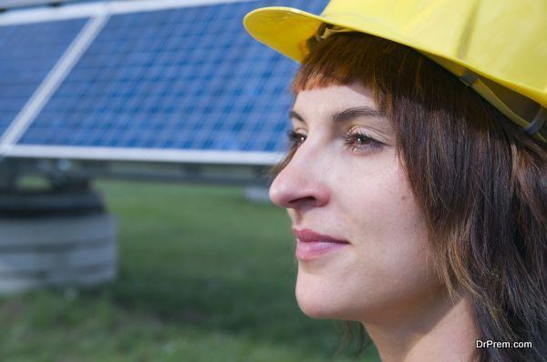 seitliches Kopfporträt einer jungen, brünetten Frau mit gelben Bauhelm als Kopfbedeckung und optimistischen Blick zur Seite
