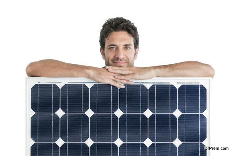 Smiling man showing and holding a solar panel isolated on white background