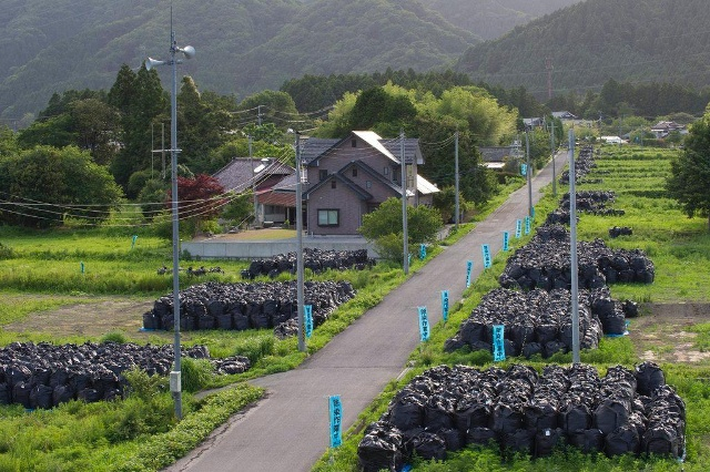 Piles of radiated soil lay along the side of a road in a deserted town near the destroyed Fukushima Daiichi nuclear power plant on June 22, 2015. (Keystone)