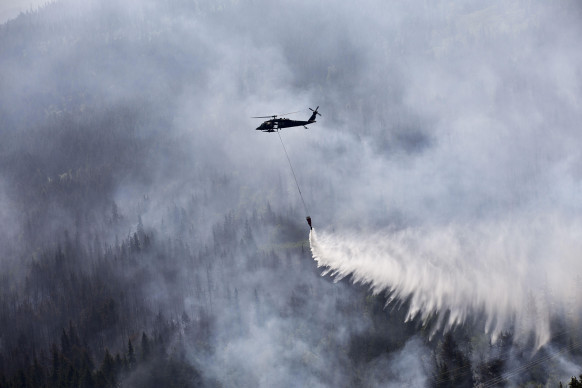 An Alaska Army National Guard helicopter drops water on afire near Cooper Landing, Alaska. Photo by Sgt. Balinda O'Neal, US Army National Guard.