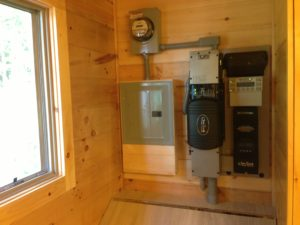 An off-grid solar system at Lake Champlain includes an Outback VFX3524 inverter, Outback FM80 charge controller, DPW top of pole rack and eight Rolls S460AGM batteries. The installer was Integrity Energy of E. Bethel, VT.