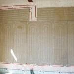 lehm-wandheizungsplatten mit integrierten warmwasserführenden Rohren werden trocken an die Wand geschraubt.