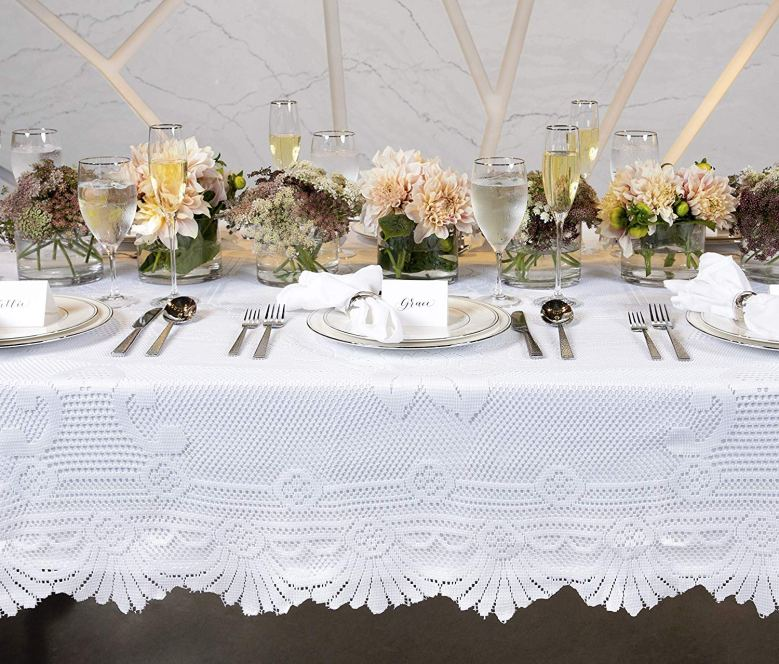 White lace tablecloth with flower arrangements and cutlery