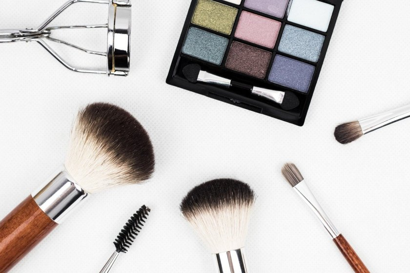 Makeup products including eyelash curler, eye shadow palette, and brushes