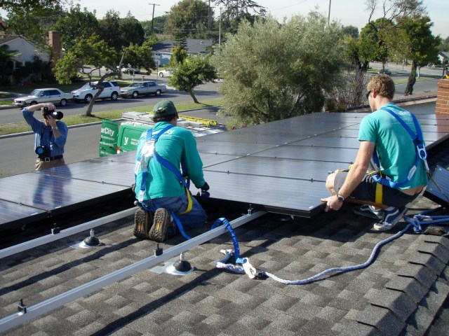 SolarCity Installers Adding Solar Panels to a Rooftop.