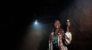 A woman uses a solar lamp provided by M-Kopa.