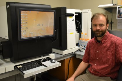 "Dr. Colin Ross, in front of a ""fast throughput"" gene sequencer"