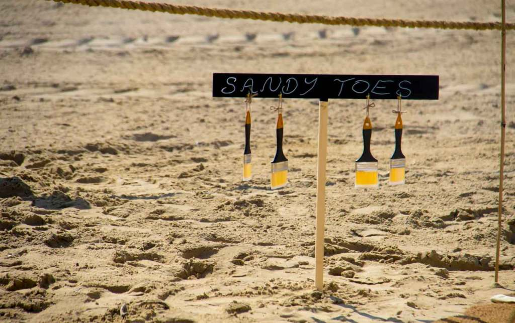 A sign in the sand that says 'sandy toes' with brushes hanging off to represent finding your way in your leadership style