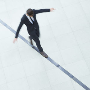 Businessman walking alone black line and trying to keep balance