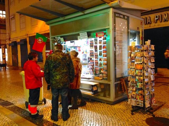 Ein Trio vor einem Kiosk in einer Querstraße der Rua Augusta in Lissabons Stadtteil Baixa.