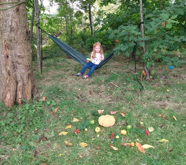 young girl sitting in hammock in the woods