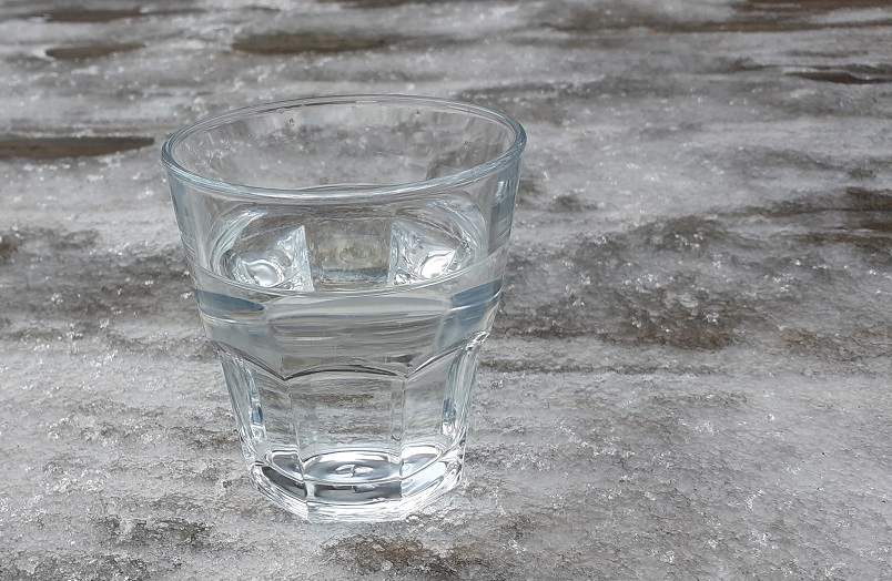 glass of water surrounded by ice