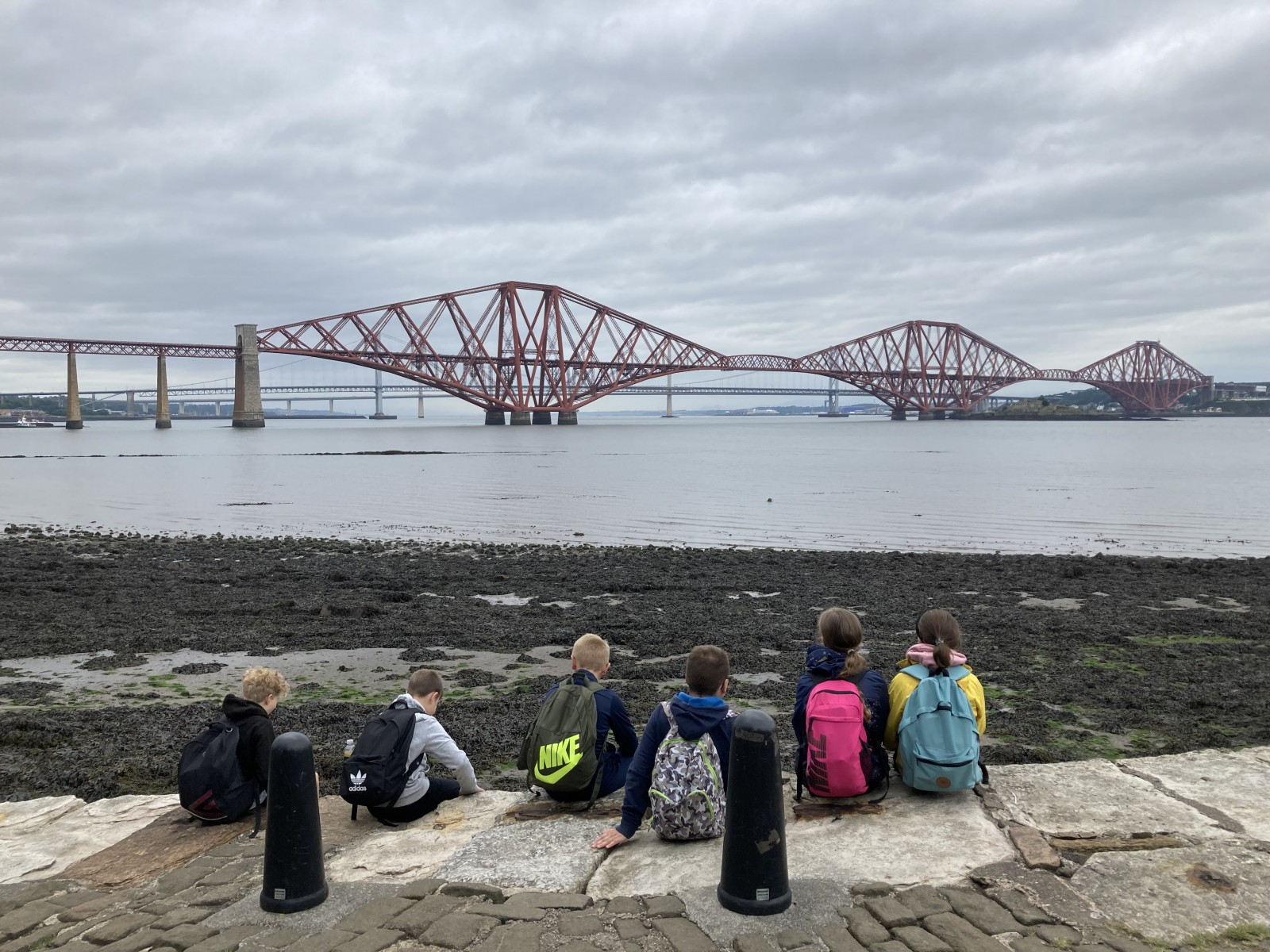 kids sitting on wall looking out to Forth Rail Bridge